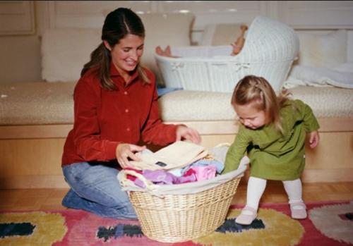 ребенок складывает игрушки в корзину